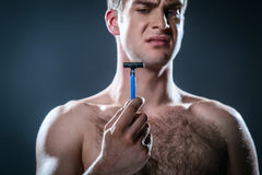 Nice concept for male beauty. Studio portrait of handsome young man. Man with naked torso having skin irritation after shaving. Man holding disposable razor Stock Images