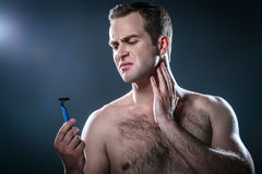 Nice concept for male beauty. Studio portrait of handsome young man. Man with naked torso having skin irritation after shaving. Man holding disposable razor Royalty Free Stock Photos