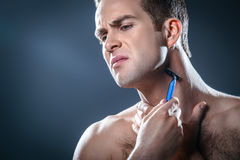 Nice concept for male beauty. Studio portrait of handsome young man. Man with naked torso having skin irritation while using disposable razor Royalty Free Stock Image