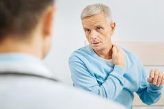 Nice concerned man touching his neck. Painful feeling. Nice concerned aged men looking at his doctor an touching the neck while being concerned about his health Royalty Free Stock Photo