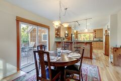 Nice country home wood kitchen with wooden island and ligth green tiles with dining room  dark cherry round table