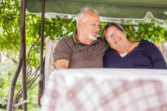 Nice couple of beautiful caucasian senior 70 years old sit outdoor at home having fun with smiles and laugh. happy life together. Forever in love and enjoy stock photography