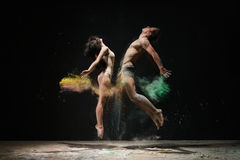 Nice couple poses in yellow and green dust cloud. Young men and women posing emotionally in jump face to face to each other in cloud of yeloow and green dust Stock Photography