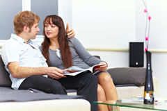 Nice couple sitting on the sofa with magazine Stock Image
