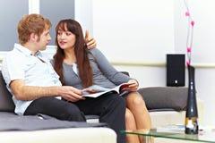 Nice couple sitting on the sofa with magazine Stock Image