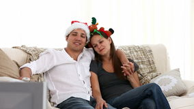 Nice couple watching tv sitting on the sofa Stock Photo