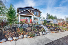 Nice Craftsman home exterior on blue sky background. Well kept frontyard with natural stone landscape design. Northwest, USA Royalty Free Stock Photos