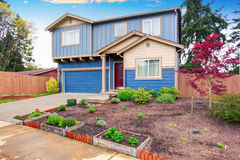 Nice curb appeal of blue house with front garden. Stock Photo