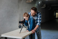 Nice curious girl standing at the table. How interesting. Nice curious pleasant girl standing at the table and looking into the telescope while spending time Royalty Free Stock Photo