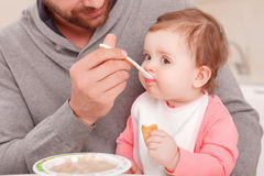 Nice daddy feeding his child Stock Photo