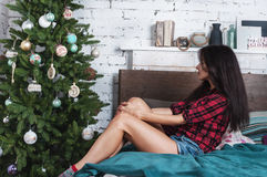 Nice dark-haired girl sits near Christmas tree. House is decorated by holiday. Nice dark-haired girl sits near Christmas tree. House is decorated by holiday royalty free stock photo
