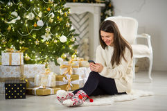 Nice dark-haired girl sits near Christmas tree with mobile phone in hands. Royalty Free Stock Images