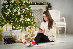 Nice dark-haired girl sits near Christmas tree with mobile phone in hands. Stock Photo
