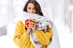 Nice dark-haired girl in a yellow sweater and a white scarf standing with a red mug on a snowy street on a winter day.  stock image