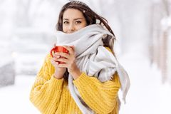 Nice dark-haired girl in a yellow sweater and a white scarf standing with a red mug on a snowy street on a winter day.  stock images
