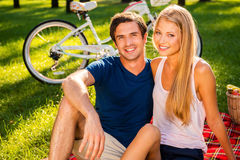 A nice day for picnic. Happy young loving couple relaxing in park together while sitting on picnic blanket and smiling while bicycle standing in the background Stock Photo