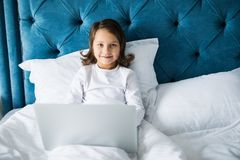 Satisfied enthusiastic little girl sitting on the bed while smiling at the camera while laptop placed in front of her royalty free stock photos