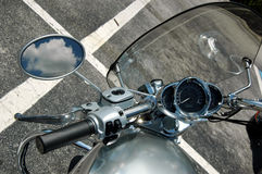 Nice day to ride. The handle, speedometer and rear-view mirror of a motorcycle with blue sky and clouds reflection in mirror Stock Images