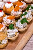 Finger food close up. Nice decorated catering on a wooden plate Stock Photos