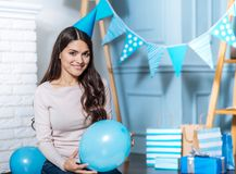 Charming young woman in party hat posing with balloon Royalty Free Stock Image