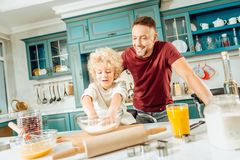 Nice delighted boy learning to make dough Stock Photos