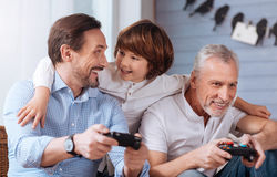Nice delighted men holding game consoles Stock Images