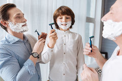 Nice delighted men holding razors. Shaving together. Nice delighted joyful men holding razor and looking at each other while shaving together stock photography