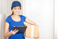 Nice deliverywoman standing near door. Checking the address. Cheerful beautiful young deliverywoman holding parcel and looking through folder while waiting near stock image