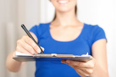 Nice deliverywoman standing near door. Just sign it. Close up of folder with pen in hands of professional deliverywoman holding them and giving to the client stock images