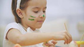 Nice den gulliga flickan har gyckel som målar ett påskägg Den förtjusande flickan colorizing Esterägget Flicka med skönhetfläckar stock video