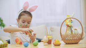 Nice den gulliga flickan har gyckel som målar ett påskägg Den förtjusande flickan colorizing Esterägget Flicka med skönhetfläckar lager videofilmer