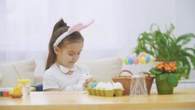 Nice den gulliga flickan har gyckel som paiting med påskkaninen, invaggar cudding den förtjusande flickan kaninen och den flicka  lager videofilmer