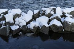 Nice details photo of snowy stones in water at winter Stock Image