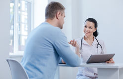 Nice doctor enjoying appointment in the hospital. Guiding you in new innovative treatment. Delighted involved skillful doctor enjoying appointment in the Stock Images