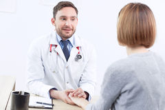 Nice doctor holding the hand of  patient Royalty Free Stock Photography