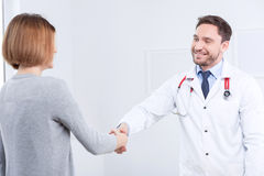 Nice doctor shaking hands with the patient Royalty Free Stock Photography