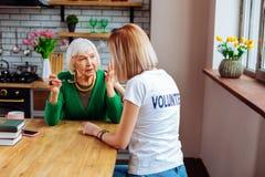 Nice-een beroep doende maatschappelijk werker troostende verouderende oma in groene wolcardigan stock fotografie