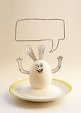 Nice egg banny on a saucer with hands smiling. Happy easter Royalty Free Stock Image