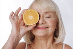 Nice elated woman putting an orange half to her eye. Citrus energy. Nice elated senior woman standing against the white background and smiling while putting an Stock Photos