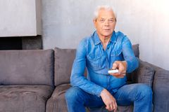 Nice elderly man holding a remote control stock image