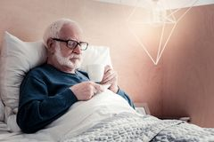 Nice elderly man lying in the bed. I need rest. Nice bearded elderly man lying in the bed and having tea while resting Stock Image