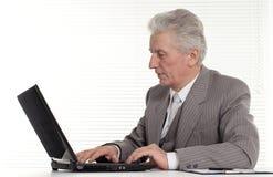 Nice elderly man sitting at the laptop Stock Image