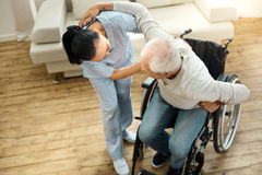 Nice elderly man using caregivers help. I need assistance. Nice pleasant elderly men leaning on the caregiver and using her help while getting up from the Stock Images