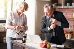 Nice elderly wife pouring coffee to her husband Stock Photo
