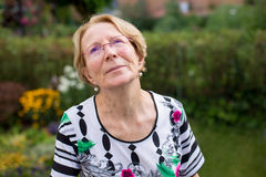 A nice elderly woman is dreaming in a beautiful garden Stock Photos