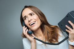 Nice emotional woman holding a phone receiver. Distance communication. Nice pleasant emotional woman holding a phone receiver and being surprised while talking Stock Image