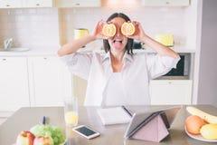 Nice en grappig beeld die van meisje haar ogen met stukken van sinaasappel verbergen Zij is opgewekt Er is tablet telefoon, notit royalty-vrije stock foto