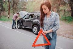 Nice en het ernstige meisje bevinden zich op de weg en houden de tekenpf rode driehoek Zij kijkt neer De kerel bevindt zich royalty-vrije stock fotografie