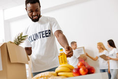 Nice enthusiastic man happy helping for free. Worthy of respect. Handsome sincere strong gentleman spending his free time working as a volunteer and packing Royalty Free Stock Photography