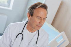 Nice experienced therapist working at the hospital. My profession. Nice experienced male therapist standing in the hospital room and thinking about his job while Royalty Free Stock Images